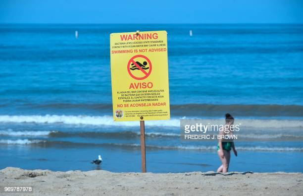 A warning sign is posted advising against swimming in the waters off Santa Monica State Beach beside Santa Monica Pier on World Oceans Day on June 8...