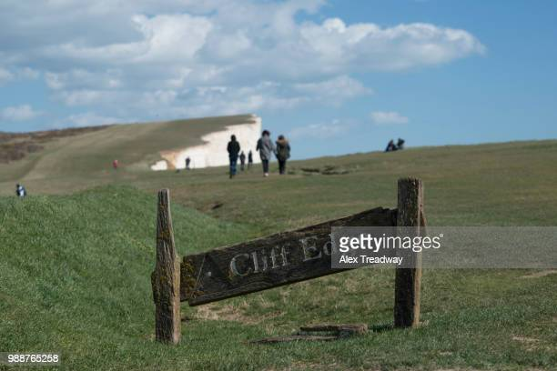 a warning sign near the cliffs at beachy head on the south coast, south downs national park, east sussex, england, united kingdom, europe - beachy head stock photos and pictures