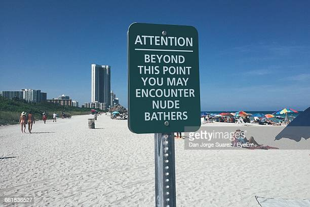 warning sign of naked sunbathers on beach - haulover beach stock photos and pictures