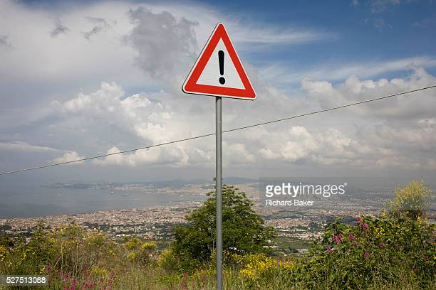 Warning sign of risk on the western slope of Vesuvius with the urban sprawl of Naples in the distance The national emergency plan to protect the...