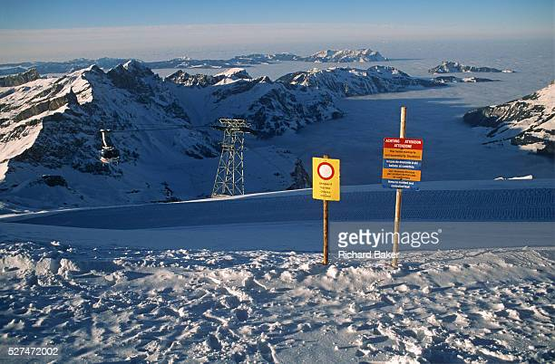 A warning sign on an alpine mountaintop for skiers tells them of a closed piste and of a no marked and controlled trail From the heights of this...