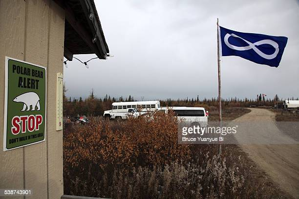 A warning sign on house with a Metis flag
