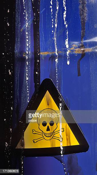 warning sign on leaking barrel with toxic waste
