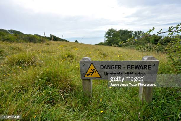 a warning sign on the coast path in devon - sign stock pictures, royalty-free photos & images