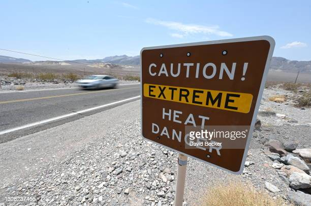 Warning sign posted alerts visitors of heat dangers on July 11, 2021 in Death Valley National Park, California. An excessive heat warning was issued...