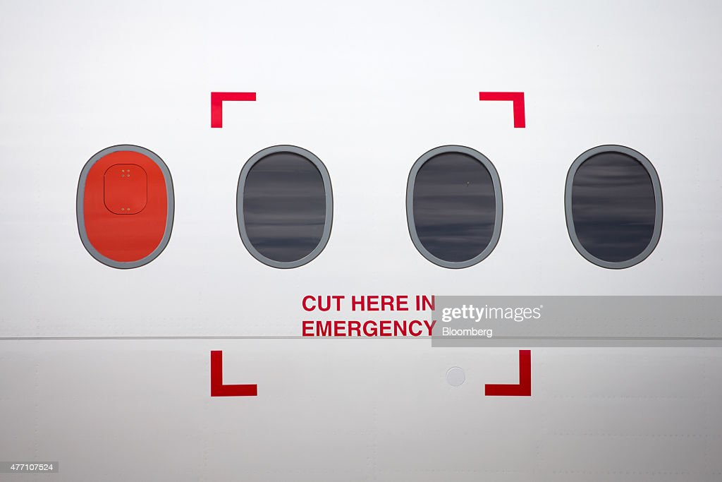 A warning sign reading 'Cut Here In Emergency' sits on the outside of the new Bombardier CS100 C Series aircraft, manufactured by Bombardier Inc., during preparations ahead of opening at the 51st International Paris Air Show in Paris, France, on Sunday, June 14, 2015. The 51st International Paris Air Show is the worlds largest aviation and space industry exhibition and takes place at Le Bourget airport June 15 - 21. Photographer: Jasper Juinen/Bloomberg via Getty Images