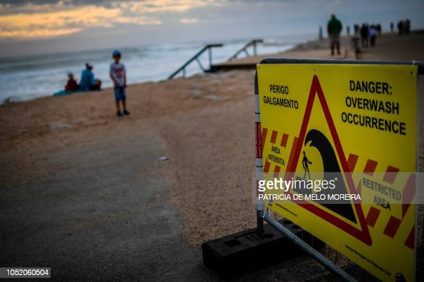"Warning sign reading ""Danger: overwash occurrence"" is displayed at Costa da Caparica, near Lisbon, on October 13, 2018. - Portugal placed most of the..."