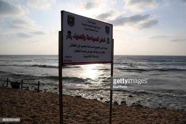 A warning sign reading 'dangerous swimming and fishing' is placed near an outlet flowing sewage into the sea in front in the Shati refugee camp in...