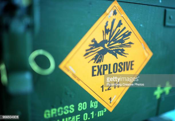 "A warning sign reading ""Explosive"" sits on a case of artillery munitions"