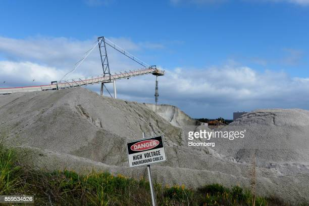 A warning sign stands as lithium ore falls from a chute onto a stockpile at a Talison Lithium Ltd facility a joint venture between Tianqi Lithium...