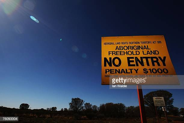 A warning sign stands at the entrance to Mutitjulu as Indigenous Affairs Minister Mal Brough meets community elders July 6 2007 in Mutitjulu near...