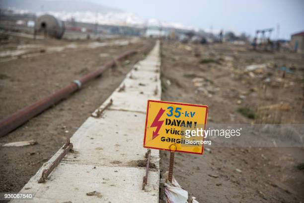 A warning sign stands in a field in Baku Azerbaijan on Sunday March 18 2018 Two years after descending into junk Azerbaijan's shortest path to...