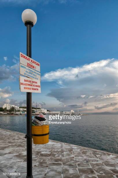 warning signs and garbage bin at the seaside. - emreturanphoto stock pictures, royalty-free photos & images