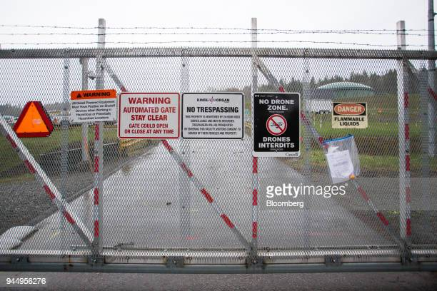 Warning signs are displayed on a fence outside of the Kinder Morgan Inc facility in Burnaby British Columbia Canada on Wednesday April 11 2018...