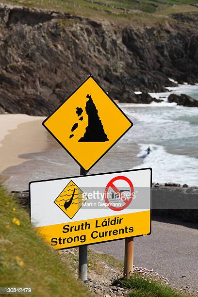 warning signs in gaelic and english, strong currents, swimming prohibited and rockfall, slea head, dingle peninsula, county kerry, ireland, british isles, europe - captions stock photos and pictures