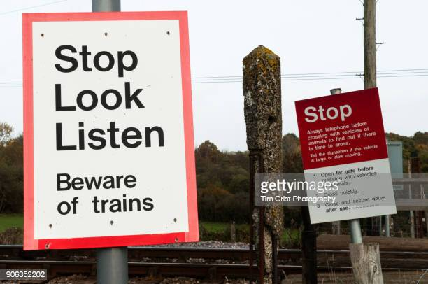 Warning signs next to a railway crossing.