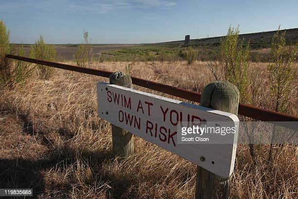 Warning to swimmers is posted along the shore of the dried O.C. Fisher Lake on July 25, 2011 in San Angelo, Texas. The 5,440 acre lake which was...