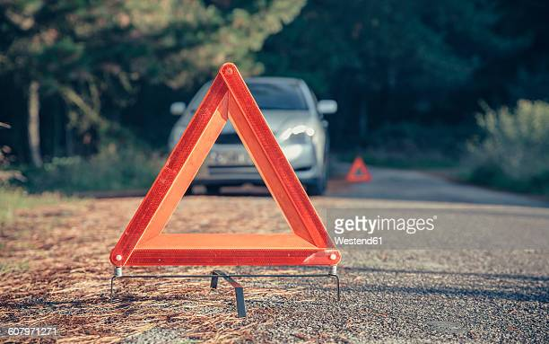 Warning triangle in the road by a car breakdown