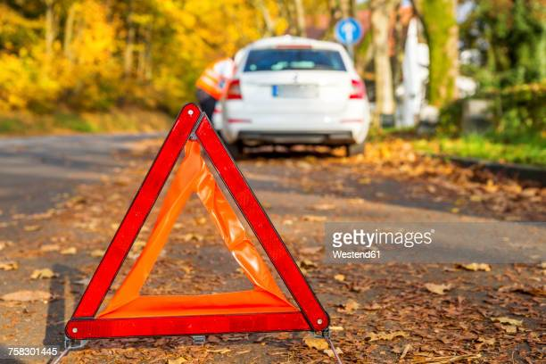 Warning triangle on the road by a car breakdown