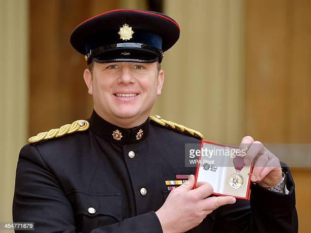Warrant Officer class1 Andy Peat holds his George Medal after it was presented to him by Queen Elizabeth II at an Investiture ceremony at Buckingham...