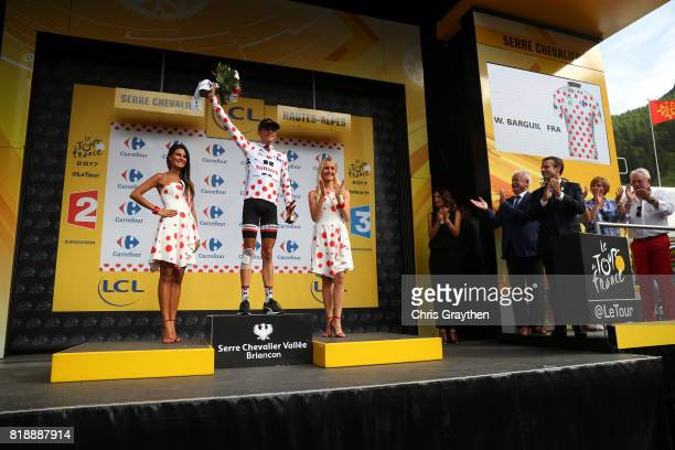 Warren Barguil of France riding for Team Sunweb stands on the podium in the king of the mountain jersey with French President Emmanuel Macron in...