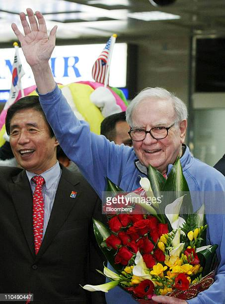 Warren Buffett chairman and chief executive officer of Berkshire Hathaway Inc right waves with Kim Bumil mayor of Daegu City as he arrives at Daegu...