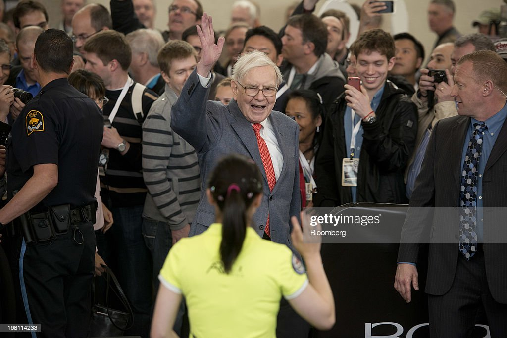 Warren Buffett, chairman and chief executive officer of Berkshire Hathaway, Inc., greets Ariel Hsing, a U.S. table tennis player, foreground in yellow, during a Berkshire shareholders event outside Borsheims Jewelry Company, Inc., in Omaha, Nebraska, U.S., on Sunday, May 5, 2013. Warren Buffett, the leader of Berkshire Hathaway since the 1960s, said the company's next chief executive officer will bolster the company's reputation as a source of stability in times of crisis. Photographer: Daniel Acker/Bloomberg via Getty Images