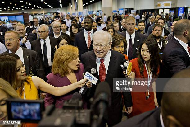 Warren Buffett chairman and chief executive officer of Berkshire Hathaway Inc center speaks with members of the media as he tours the exhibition...
