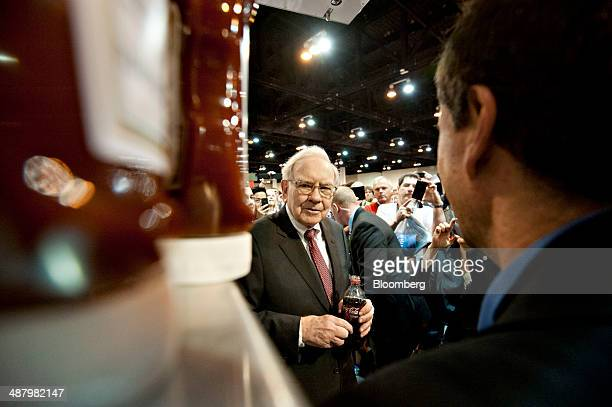 Warren Buffett chairman of Berkshire Hathaway Inc discusses Heinz ketchup bottles bearing his likeness as he tours the exhibition floor flanked by...
