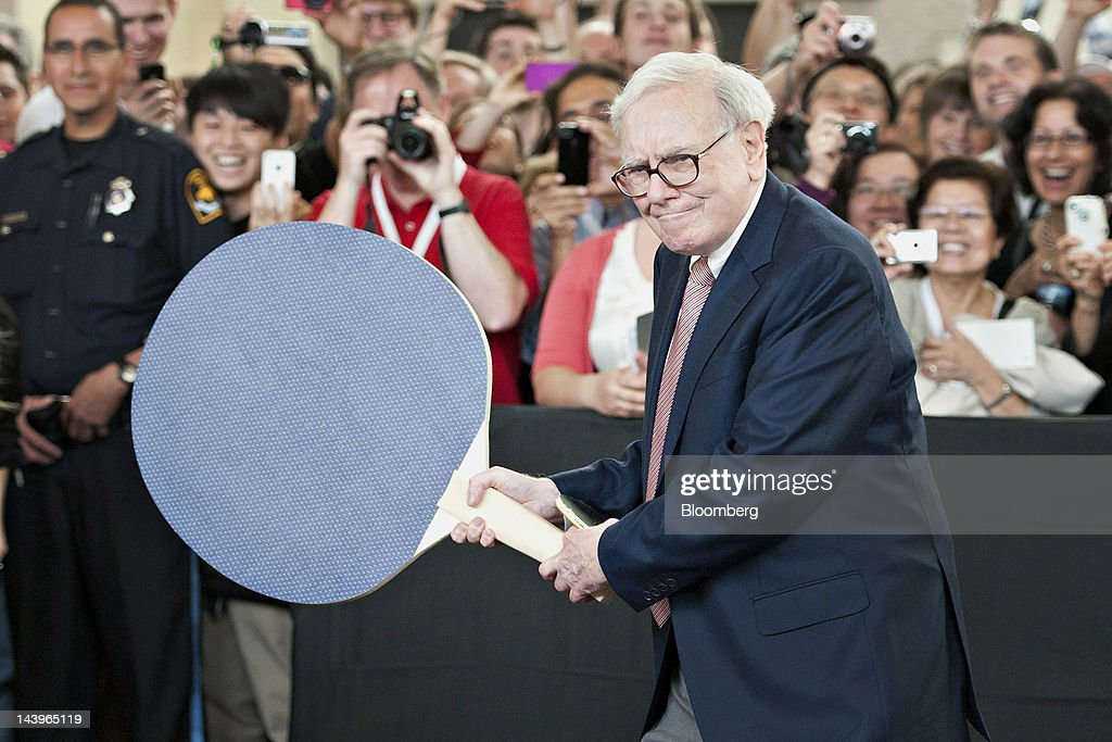 Warren Buffett, chairman of Berkshire Hathaway Inc., holds a large ping pong paddle as he plays table tennis with Ariel Hsing, a member of the 2012 U.S. Olympic team, during an event at the annual shareholders meeting in Omaha, Nebraska, U.S., on Sunday, May 6, 2012. Berkshire Hathaway Inc. investment managers Todd Combs and Ted Weschler receive $1 million salaries and can earn more if their bets beat the Standard & Poor's 500 Index, Buffett said Sunday. Photographer: Daniel Acker/Bloomberg via Getty Images