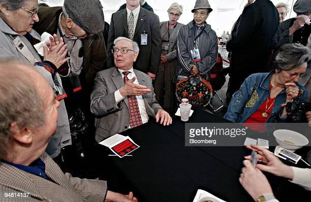 Warren Buffett chairman of Berkshire Hathaway Inc seated left speaks to a Berkshire Hathaway shareholder while playing bridge at the company's annual...