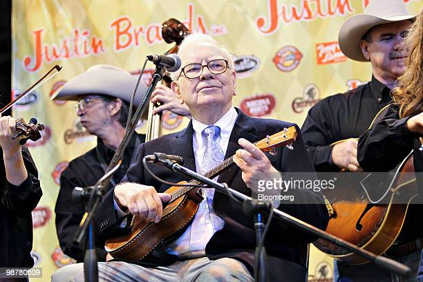 Warren Buffett chief executive officer of Berkshire Hathaway plays the ukulele during a tour of the exhibition floor prior to the Berkshire Hathaway...