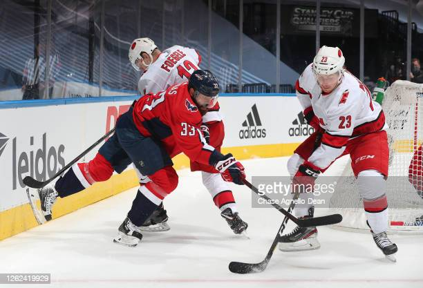 Warren Foegele and Brock McGinn of the Carolina Hurricanes vie for position against Radko Gudas of the Washington Capitals in the first period of an...