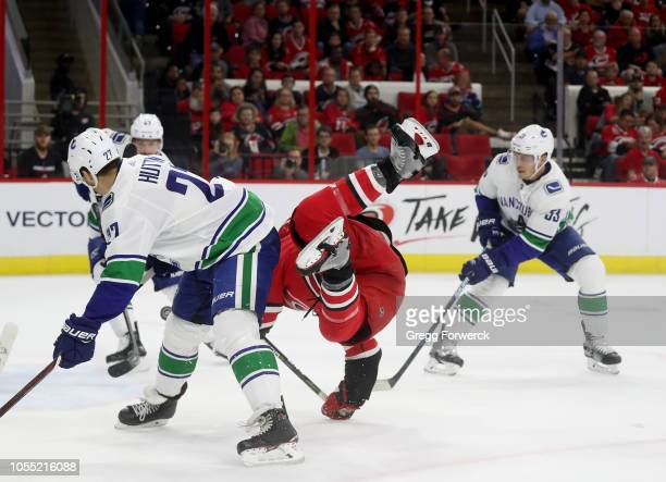 Warren Foegele of the Carolina Hurricanes is tripped up near the crease as Ben Hutton and Bo Hovat of the Vancouver Canucks defend during an NHL game...