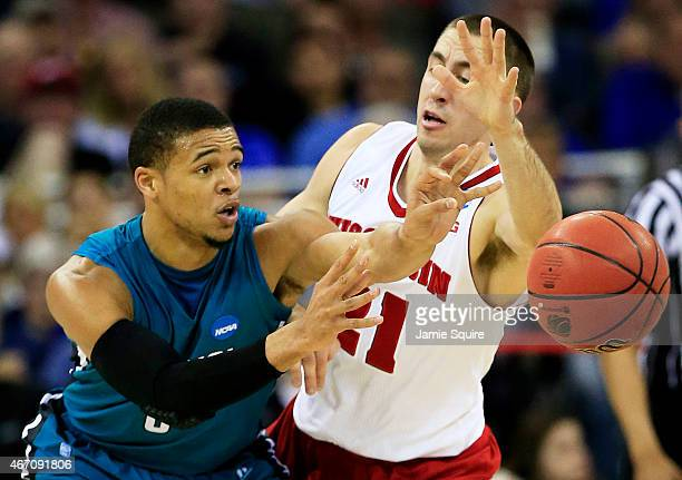 Warren Gillis of the Coastal Carolina Chanticleers passes around Josh Gasser of the Wisconsin Badgers in the first half during the second round of...