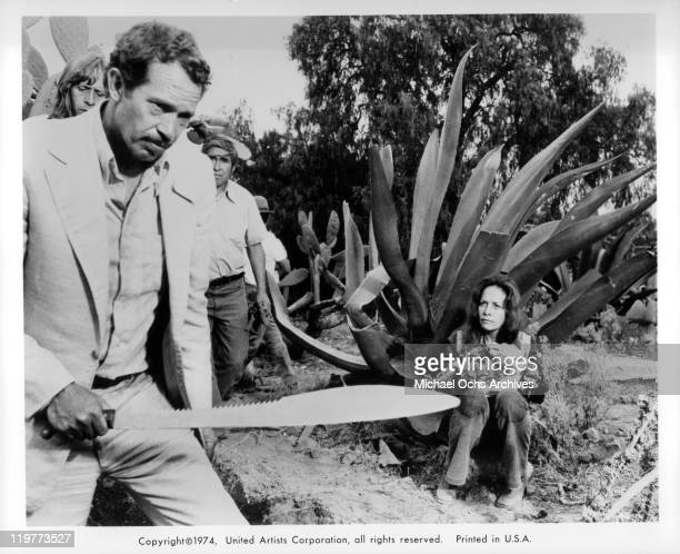 Warren Oates with large knife as Isela Vega sits in a scene from the film 'Bring Me the Head of Alfredo Garcia' 1974