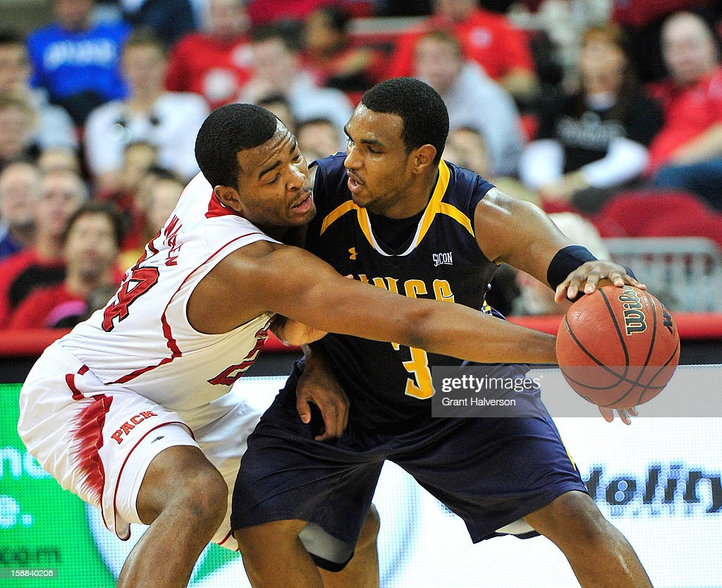 T.J. Warren #24 of the North Carolina State Wolfpack defends against Derrell Armstrong #3 of the UNC Greensboro Spartans during play at PNC Arena on December 31, 2012 in Raleigh, North Carolina. North Carolina State won 89-68.