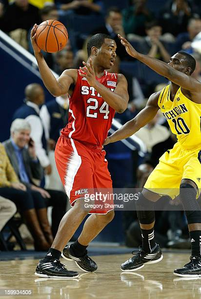 J Warren of the North Carolina State Wolfpack tries to get around the defense of Tim Hardaway Jr #10 of the Michigan Wolverines at Crisler Center on...