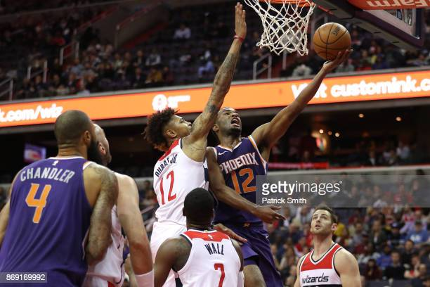Warren of the Phoenix Suns shoots in front of Kelly Oubre Jr #12 of the Washington Wizards during the second half at Capital One Arena on November 01...