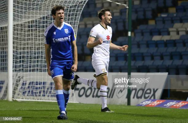Warren O'Hora of Milton Keynes Dons celebrates after scoring his sides second goal as Thomas O'Connor of Gillingham FC reacts during the Sky Bet...