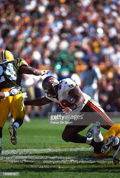 Warren Sapp of the Tampa Bay Buccaneers attempts to tackle Aaron Hayden of the Green Bay Packers during an NFL football game at Lambeau Field October...