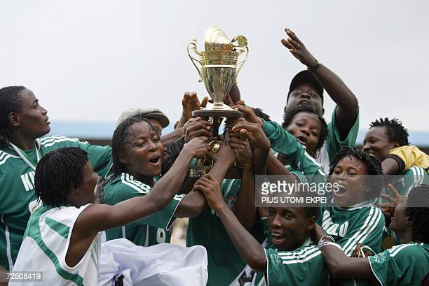 Nigerian female national team the Super Falcons celebrate with the trophy won at the end of encounter with their Ghanaian counterpart at the Warri...