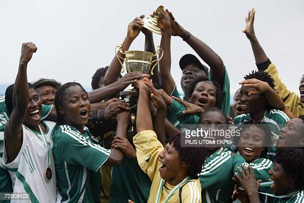 The Nigerian female national football team the Super Falcons celebrate with the trophy won at the end of encounter with their Ghanaian counterpart at...