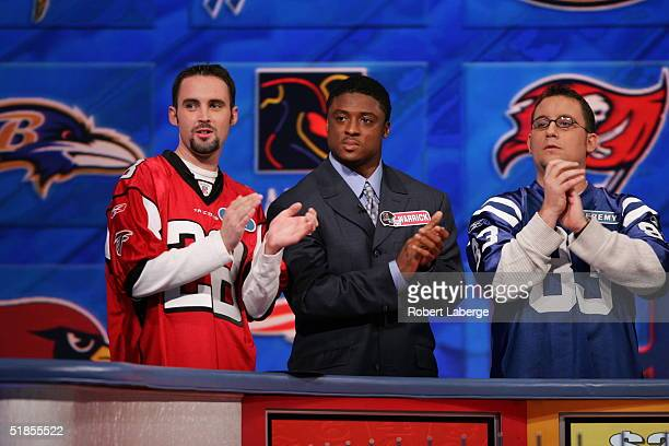 Warrick Dunn of the Atlanta Falcons applauds with his favorite Falcons fan during the Wheel of Fortune NFL Players Week taping on December 7 2004 at...