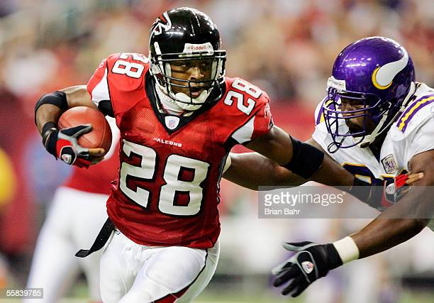 Warrick Dunn of the Atlanta Falcons foists off defensive tackle Spencer Johnson of the Minnesota Vikings in the third quarter on October 2, 2005 at...