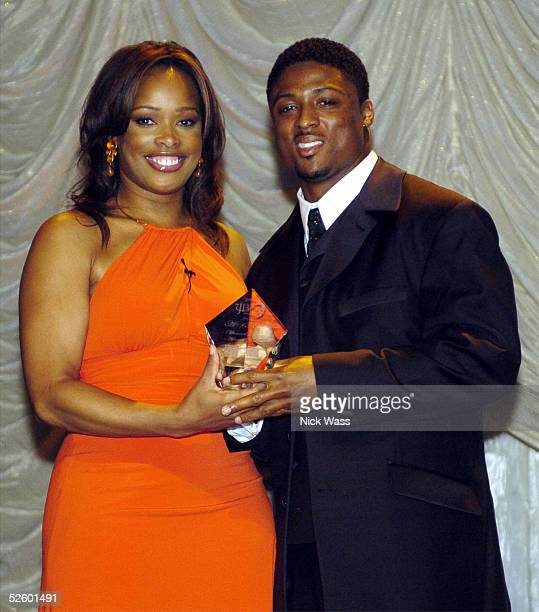 Warrick Dunn of the Atlanta Falcons poses with Pam Oliver Fox sports personality left as he is awarded the JB award for an Act of Kindness during the...