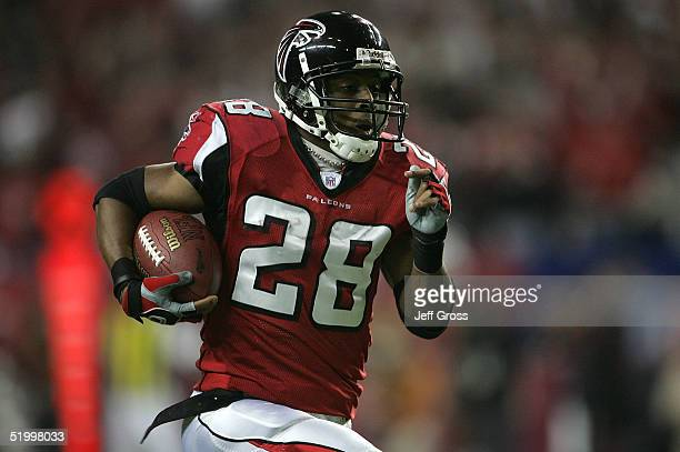 Warrick Dunn of the Atlanta Falcons runs for a 62 yard touchdown against the defense of the St Louis Rams during first quarter of the NFC Divisional...