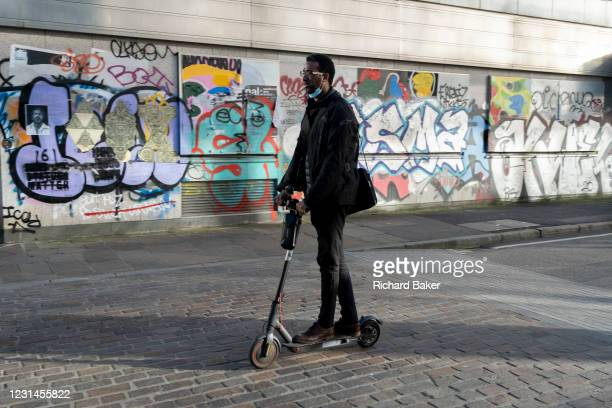 Warring a face covering on his chin, a commuter rides an eScooter past the graffiti on the exterior of a former office property in during the third...