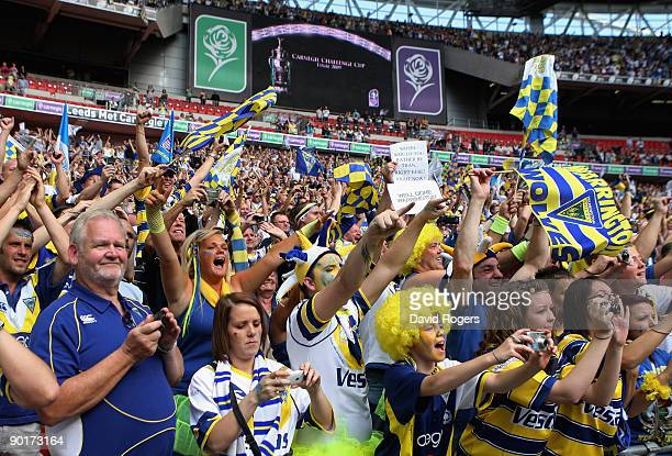 Warrington fans celebrate following their teams victory during the Carnegie Challenge Cup Final between Huddersfield Giants and Warrington Wolves at...