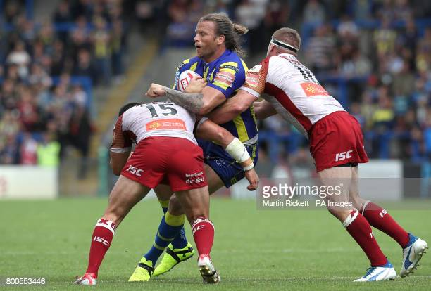 Warrington Wolves' Ashton Sims is tackled by Catalans Dragons' Benjamin Garcia and Remi Casty during the Betfred Super League match at the Halliwell...